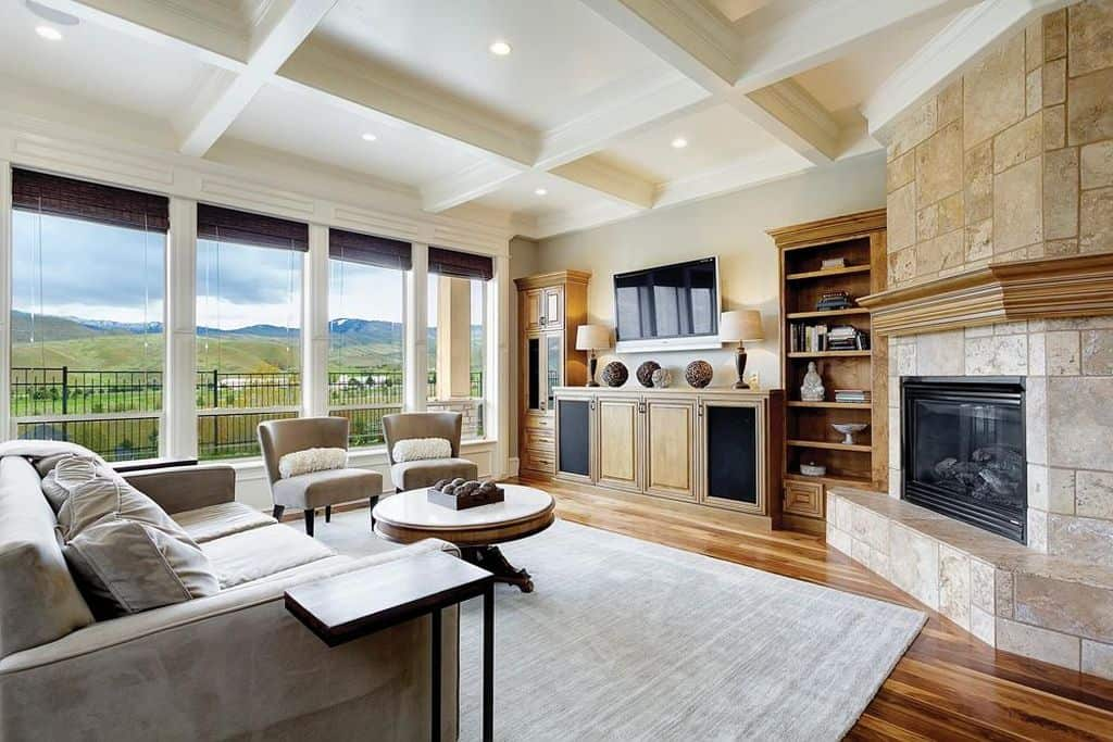 Fresh living room offers hardwood flooring and glass paneled windows overlooking the spectacular mountains and hills. There's a fireplace in the corner fitted on the stone brick pillar lined with wooden mantel and white crown molding.