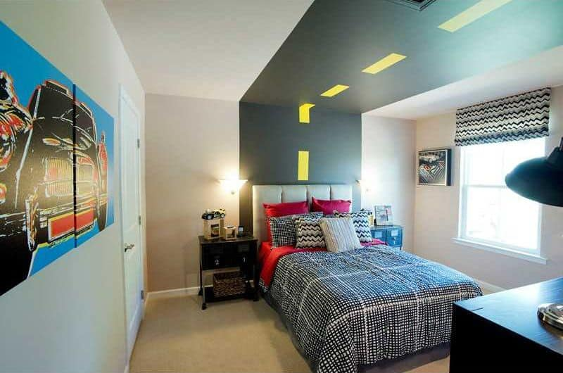 This boy's bedroom features stylish wall designs, along with carpet flooring and beautiful lighting.