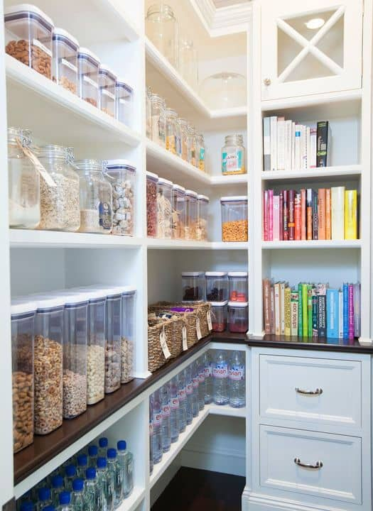 A close up look at this pantry's white shelving and cabinetry.