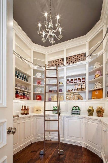 This pantry with white shelving and a counter also features a marble countertop. There's a ladder too, set on the hardwood flooring.