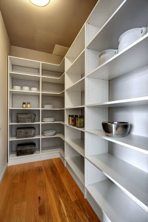 This pantry offers white shelving together with hardwood flooring.