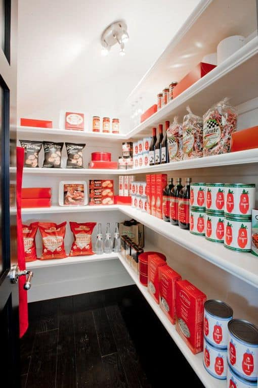A small walk-in pantry with an espresso finish hardwood flooring and door together with white walls and shelving.