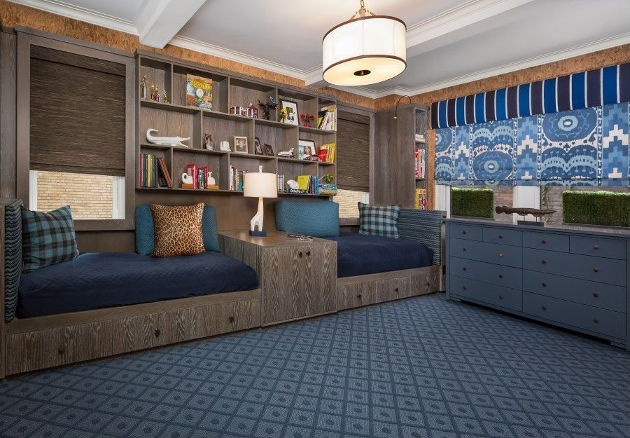 Large boy's bedroom boasting blueish gray floors and cabinetry. The beds are very attractive together with the pendant lighting.