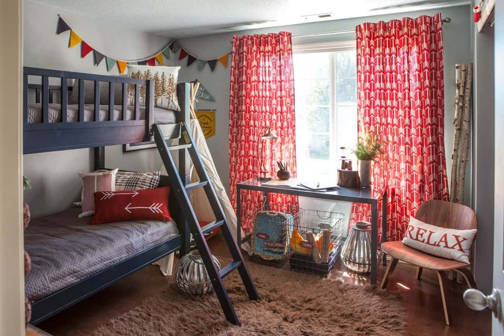 Small boy's bedroom with a bunk bed and a classy rug, along with red window curtains.
