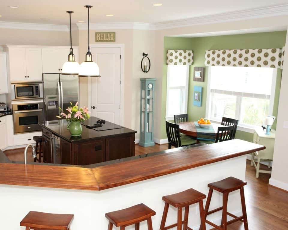 Eat-in kitchen with green walls to separate the small dining area by the window and a peninsula island with wood surface and matching bar stools.
