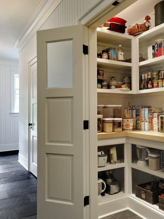 A small walk-in pantry with a thick plank countertop and white cabinetry and shelving.