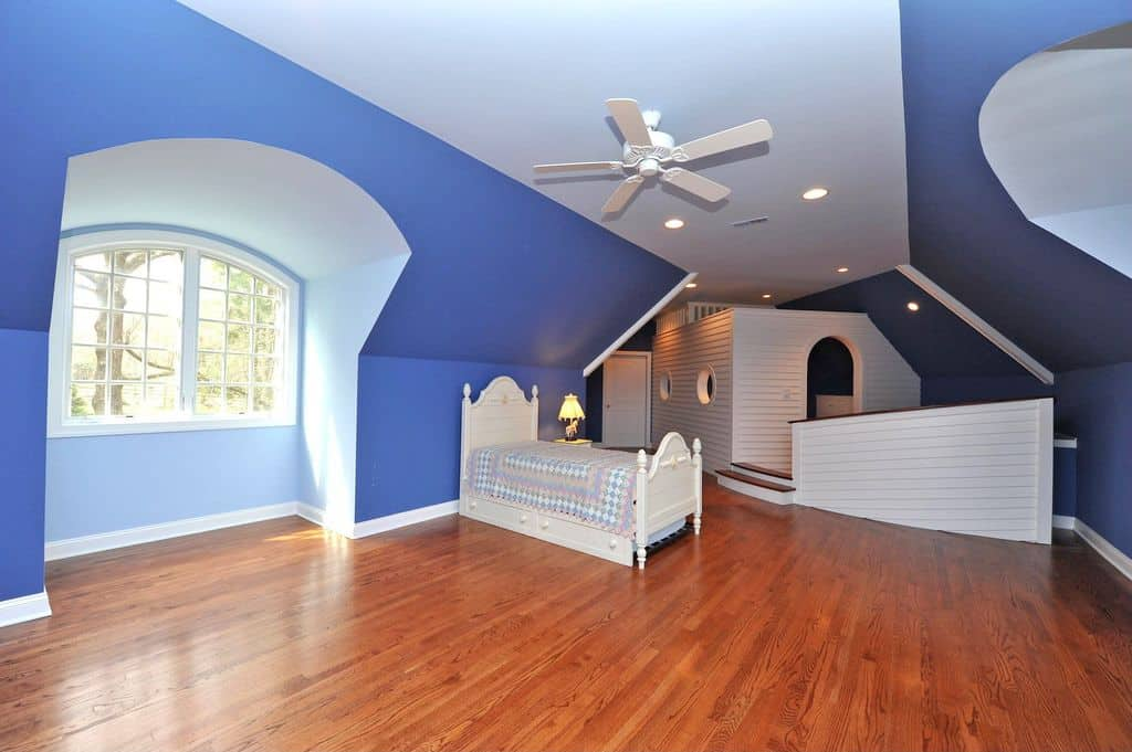 Large boy's bedroom with indigo-finished walls and stylish room design, along with the hardwood flooring.