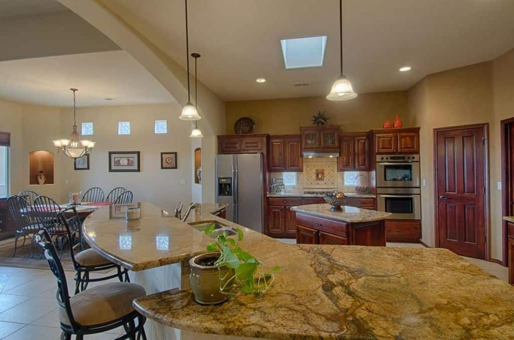This kitchen features a small center island and a peninsula, both with marble countertops.