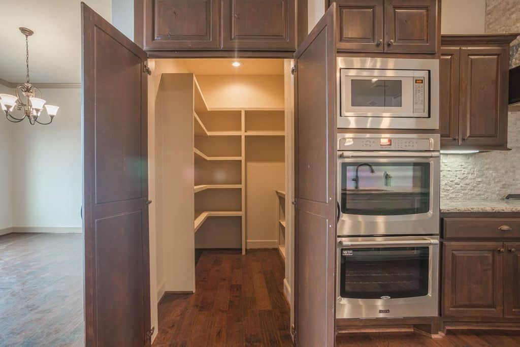 This beautiful kitchen also features a walk-in pantry with white walls and shelving along with hardwood flooring.