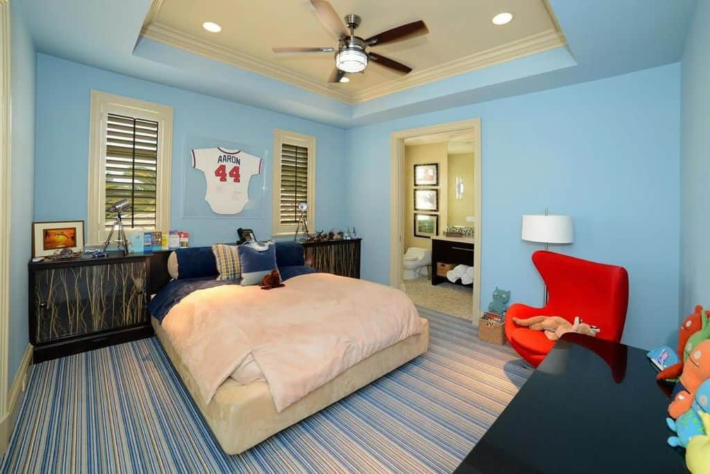 Boy's bedroom featuring blue walls and a tray ceiling along with stylish carpet flooring. The room also has its own bathroom.