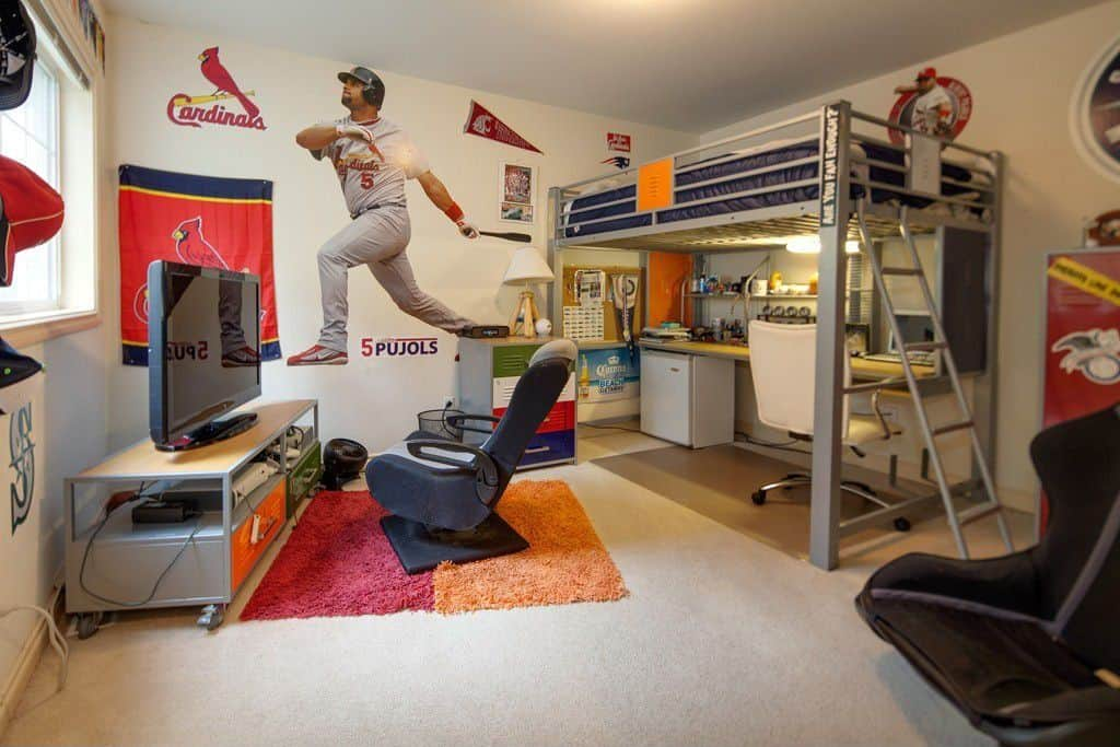 This boy's bedroom boasts baseball-inspired walls with carpet flooring. The bed and desk combo look very stylish. The gaming set up is very charming too.