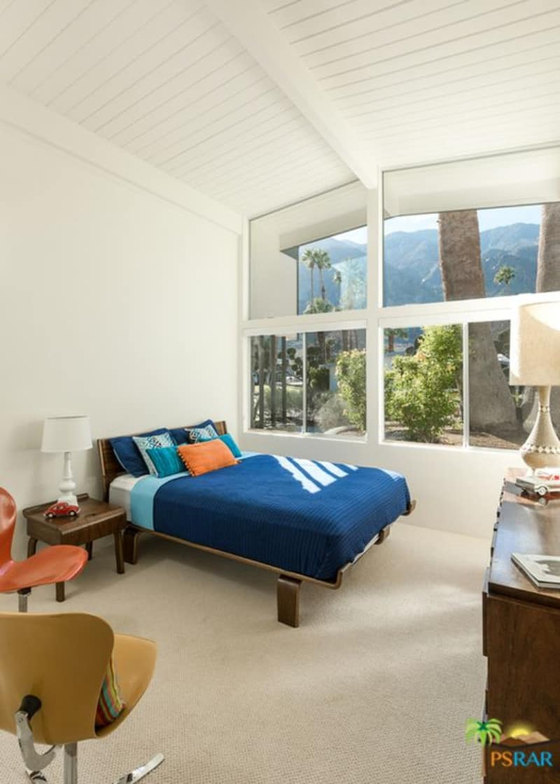 White guest bedroom boasts contemporary chairs and a lovely blue bed by the glass picture windows overlooking the outdoor scenery.