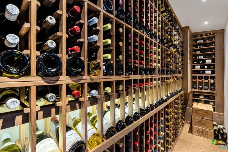 Custom floor to ceiling built-in wood wine rack that showcases a massive display of bottles.