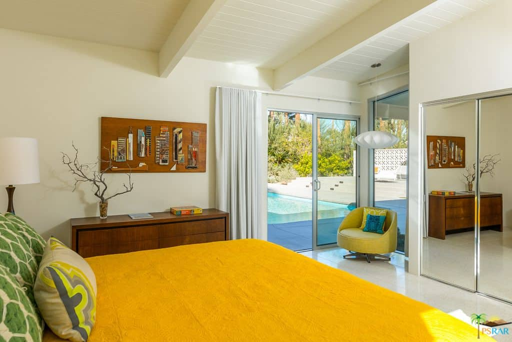 Vibrant yellow bed and round back chair lighted by a white pendant stand out in this cream bedroom with tiled flooring and wood beam ceiling.