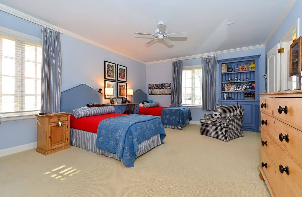 Large boy's bedroom with light blue walls and carpet flooring. The table lamps on the table set on the middle of the two beds look beautiful as well.