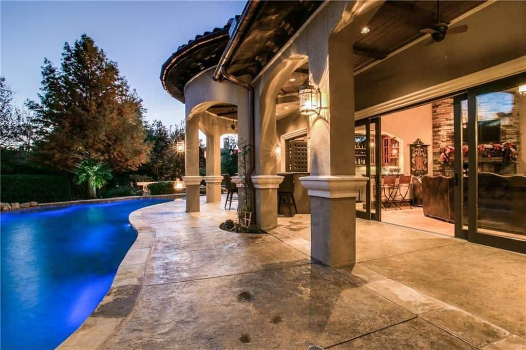 Luxurious patio area lighted by wall lighting and recessed lights.