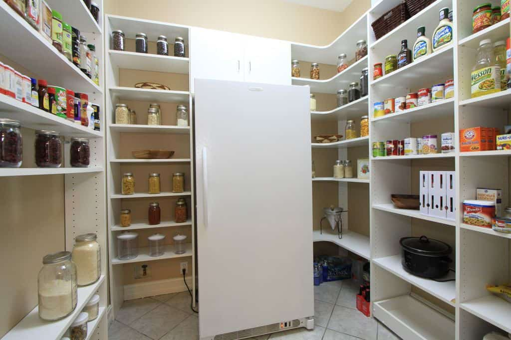 Large walk-in pantry featuring white shelving, white tiles flooring and a white fridge.