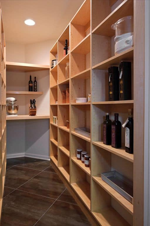 This pantry boasts walnut finished shelving together with stylish tiles flooring.
