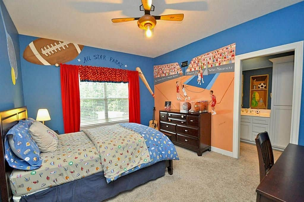 This boy's bedroom features athletically inspired wall designs and carpet flooring.