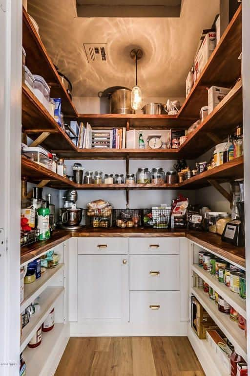 This small pantry features white counters and rustic shelving matching the hardwood flooring.