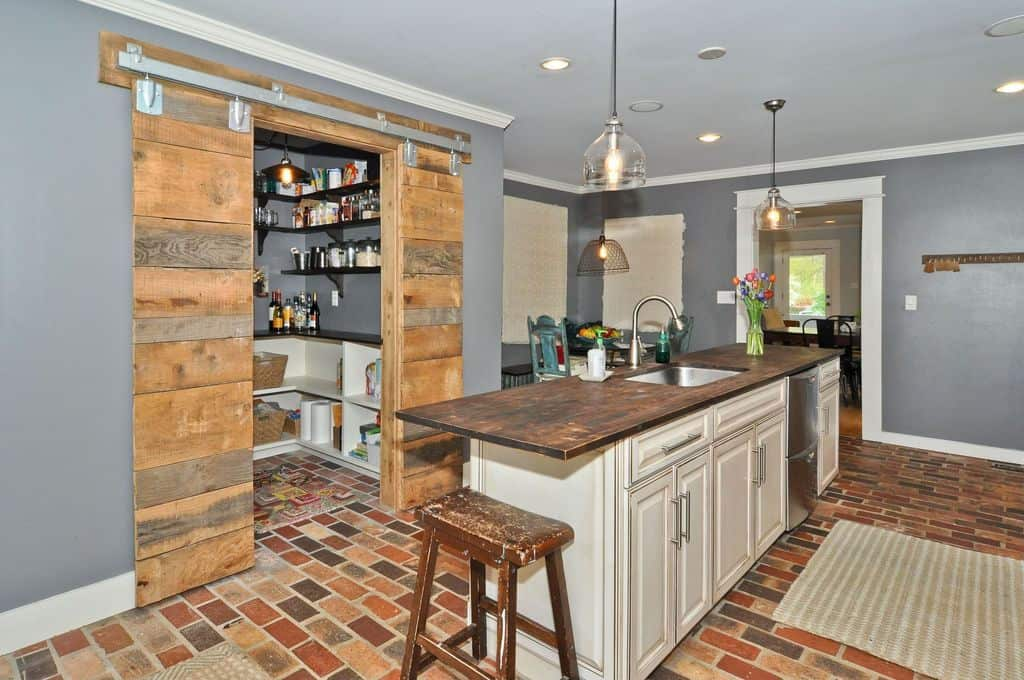 A rustic kitchen with a stylish center island along with a walk-in pantry with espresso finished shelves and countertop.