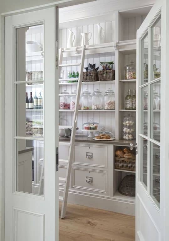 This walk-in pantry features hardwood flooring along with a ladder. White walls fit well with the white cabinetry and shelving.