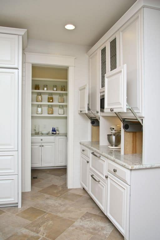 This kitchen features a small pantry with white shelving and counters.