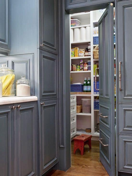 A small walk-in pantry with gray doors matching the kitchen's gray finish shade.