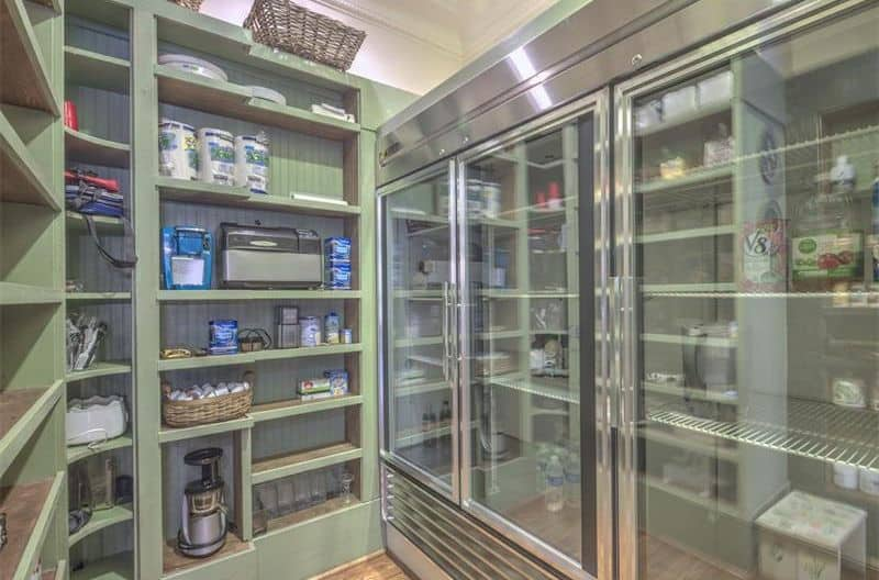 This pantry boasts a green finished shelving along with the hardwood flooring.