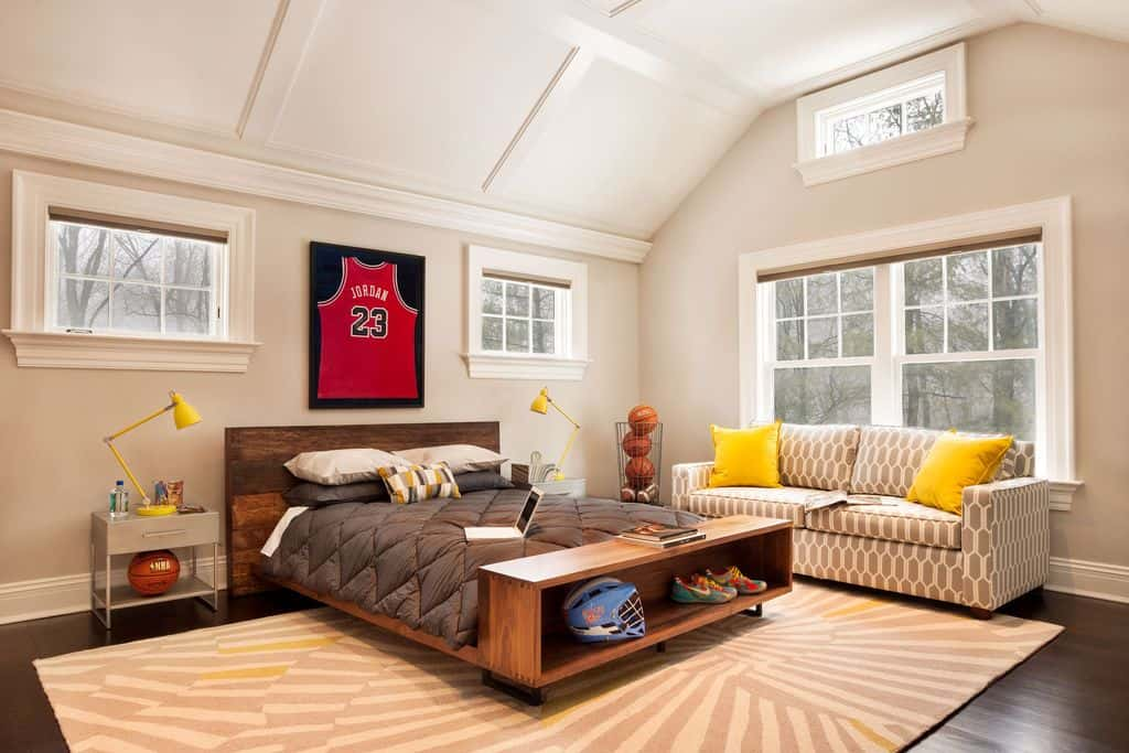 Large boy's bedroom boasting a large bed and a couch near the windows, set on the hardwood flooring topped by a classy rug.