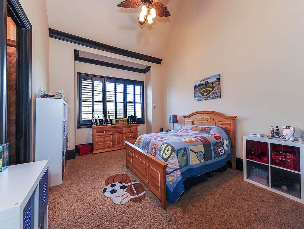 This boy's bedroom boasts lovely carpet flooring, along with white walls lighted by a charming ceiling light.