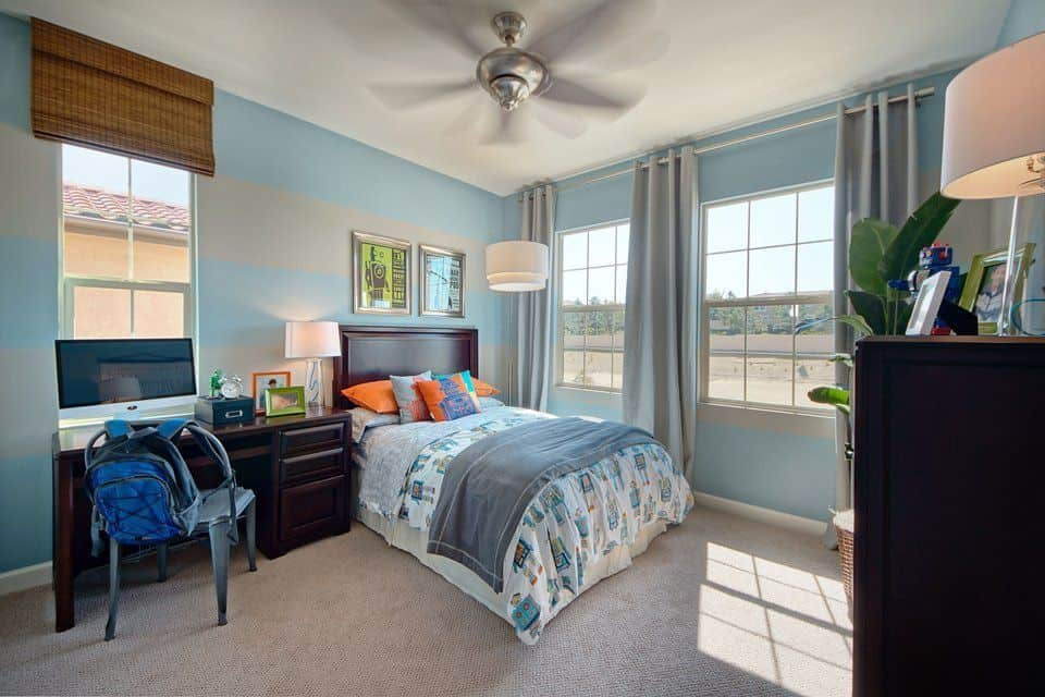 This boy's bedroom features blue and gray walls, matching the gray carpet flooring and gray window curtains.