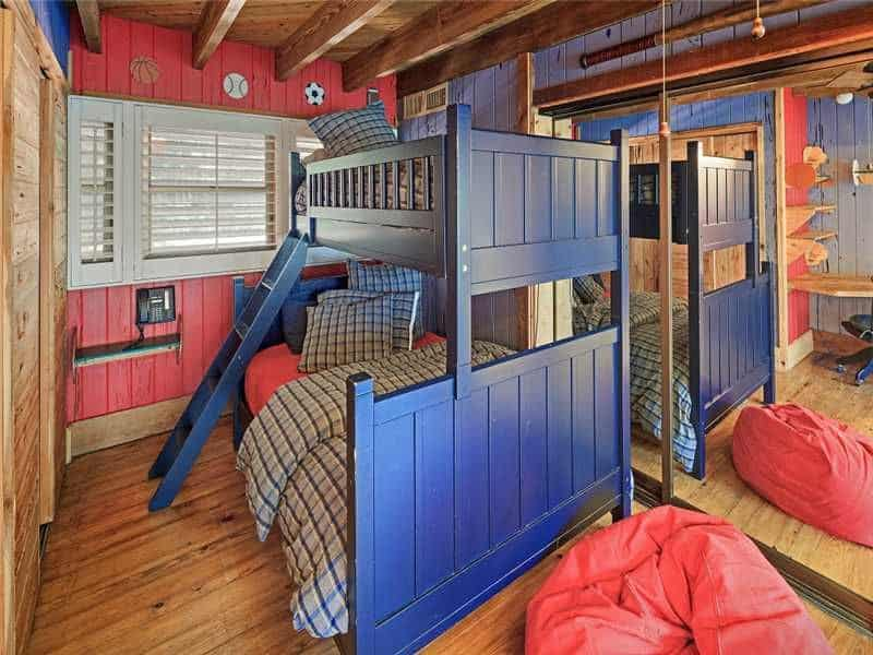 This boy's bedroom boasts two bunk beds set on the hardwood flooring, that matches the wooden walls with different colors.