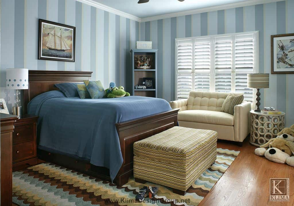 This boy's bedroom features stylish striped blue walls, along with a small couch and a large bed set on the hardwood flooring topped by a classy rug.