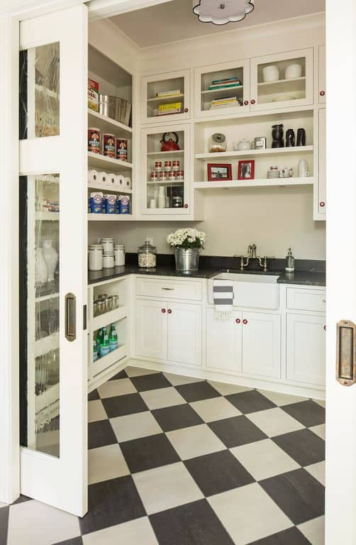Large walk-in pantry offering multiple cabinets and shelves, along with white counters with black granite countertops. The checker flooring looks stylish as well.