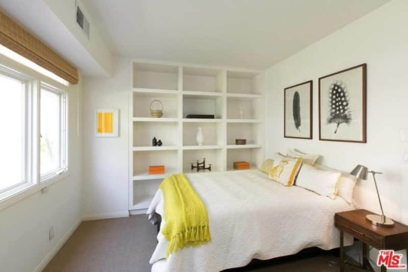 A pair of framed wall arts hang above the comfy bed in this white guest bedroom with open shelving and wooden nightstand topped with a chrome table lamp.