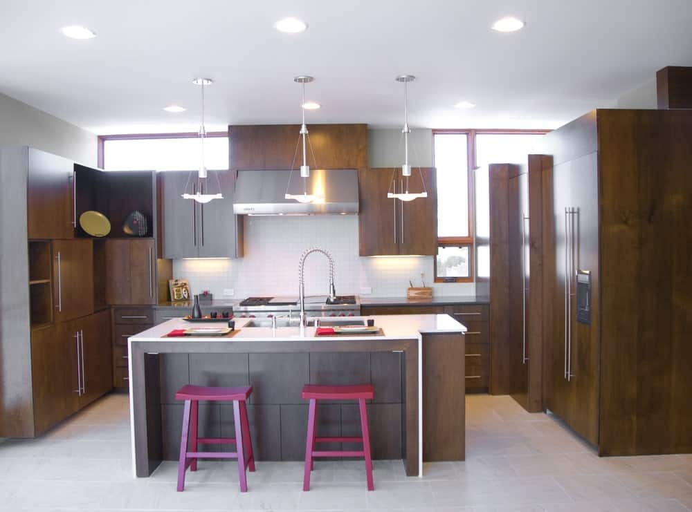 A pair of magenta bar stools sit on a wooden breakfast island that matches with the natural wood cabinetry in this kitchen. It is fitted with dual sink and a chrome spring pull-down faucet.