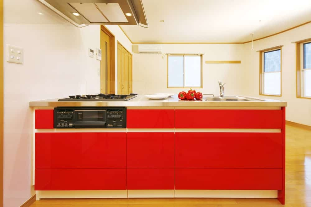 A white kitchen boasts a red peninsula with stainless steel countertop and sink. It also has a built-in cooktop with vent hood mounted on the white ceiling.
