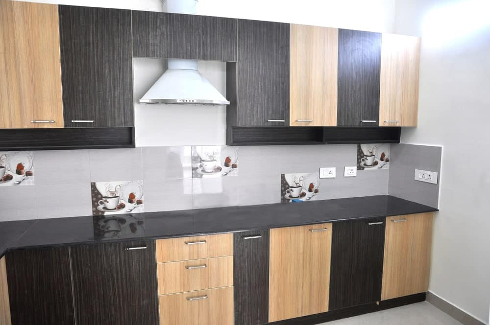 Asian style kitchen with a combination of dark and light wood cabinetry along with gray tile backsplash accented with coffee decorative tiles.