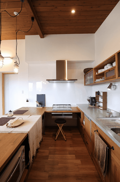 A black stool sits on a wooden counter in this warm kitchen fitted with a built-in cooktop. It has a wood plank ceiling and hardwood flooring.