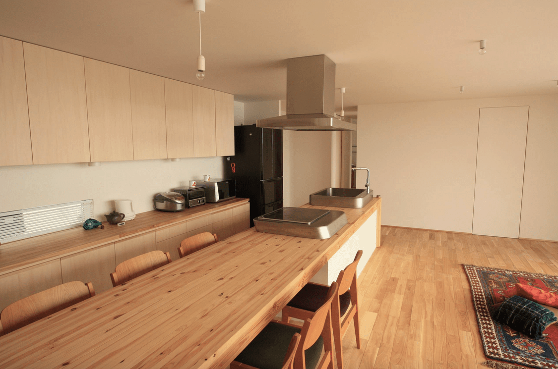 An open kitchen with a lengthy breakfast bar fixed with a vessel sink and cooktop. It is aligned with wooden chairs fitted with black cushions over hardwood flooring.