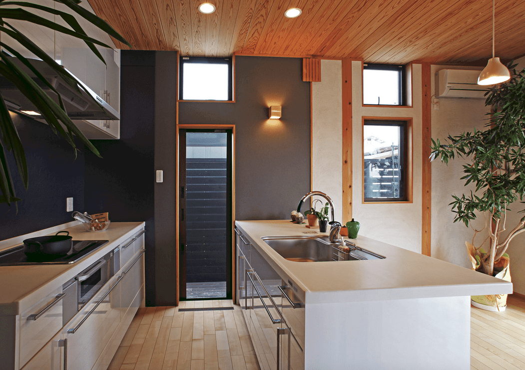 This kitchen offers sleek cabinetry with pearl white granite countertops. It is illuminated by recessed ceiling lights and a modern sconce mounted on the gray wall.