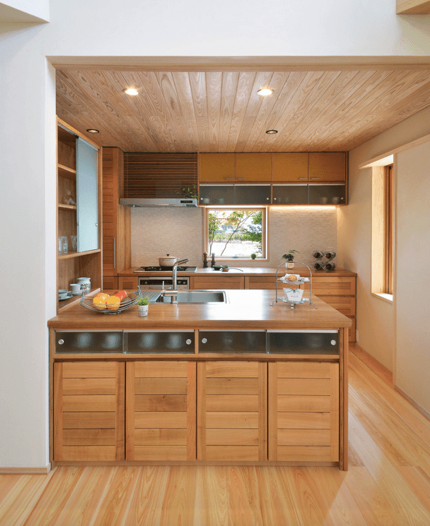 Asian style kitchen boasts wood cabinetry lined with frosted glass front storage units. It includes white mosaic tile backsplash fitted with a small glass window.
