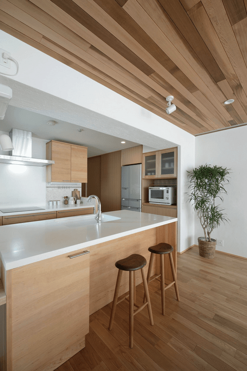 Cozy kitchen features light wood cabinetry that complements with the wood plank flooring and ceiling. There's an indoor plant in the corner that gives life to the area.