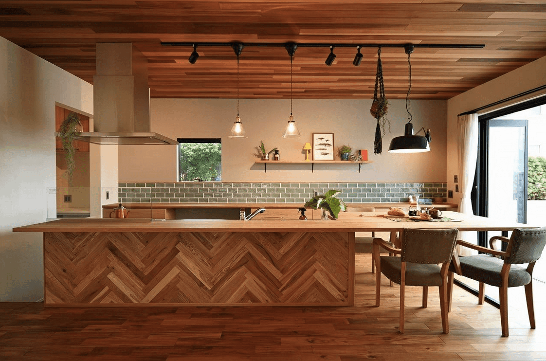 Sophisticated kitchen showcases a lengthy herringbone breakfast bar with cushioned counter chairs. It has wooden cabinetry accented by a sage green subway tile backsplash.