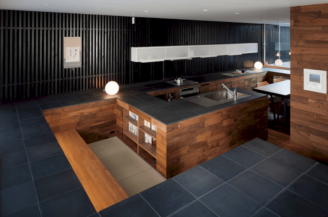 Asian style kitchen boasts wood plank peninsula topped with black tile counter that complements with the vertical wood slat wall mounted with white glass front cabinetry.