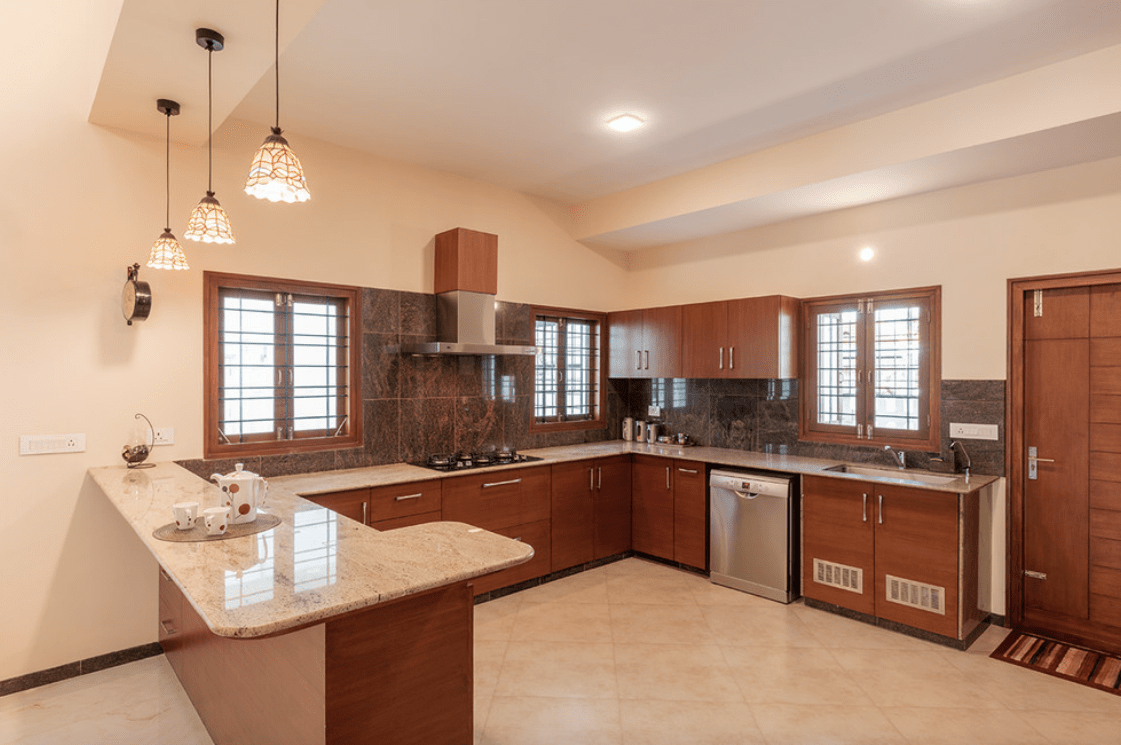This kitchen features wood cabinetry and a beige marble top peninsula illuminated by fancy pendants. It has a stainless steel vent hood fixed to the black marble backsplash tile.
