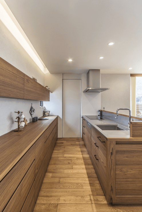 Galley kitchen with wood plank flooring that complements with the natural wood cabinetry creating a cohesive look.