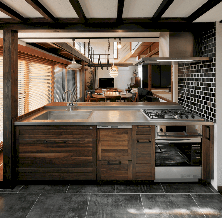 Gorgeous kitchen accented with a black subway tile wall fixed with a stainless steel range hood that hung over a cooktop. It has concrete tiled flooring and white ceiling with exposed wood beams.