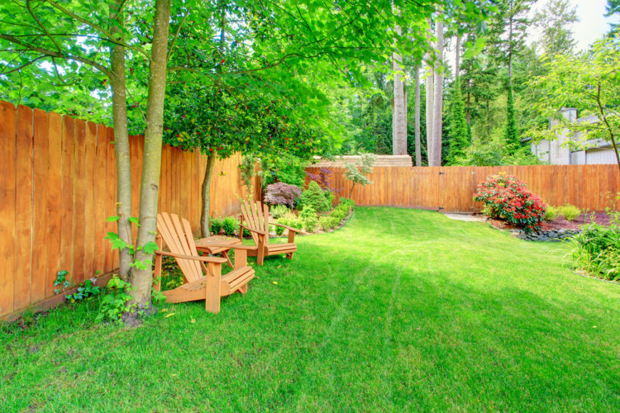Backyard with great wooden fence and two adirondack chairs.